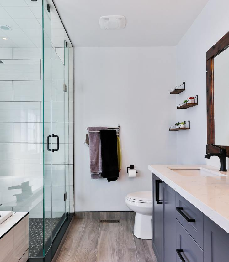 Image of a bathroom, including a bath tub and shower, and big mirror with cupboards